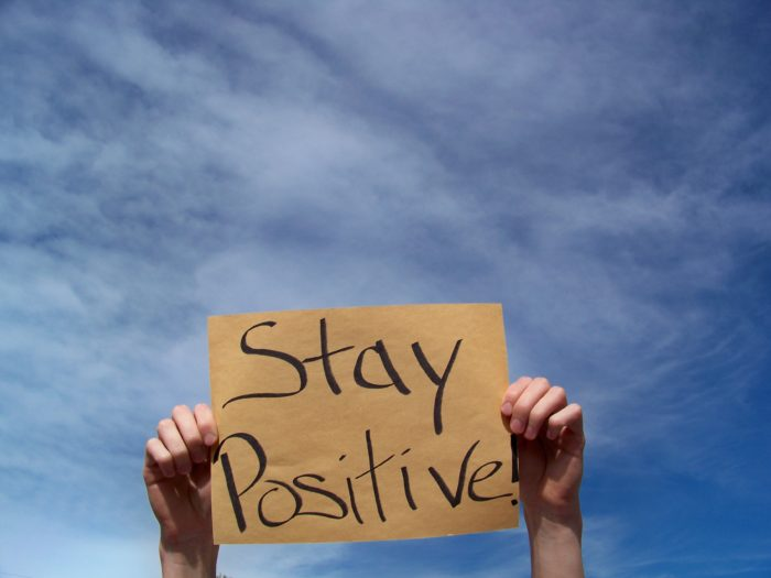 Hands holding a sign up that says stay positive