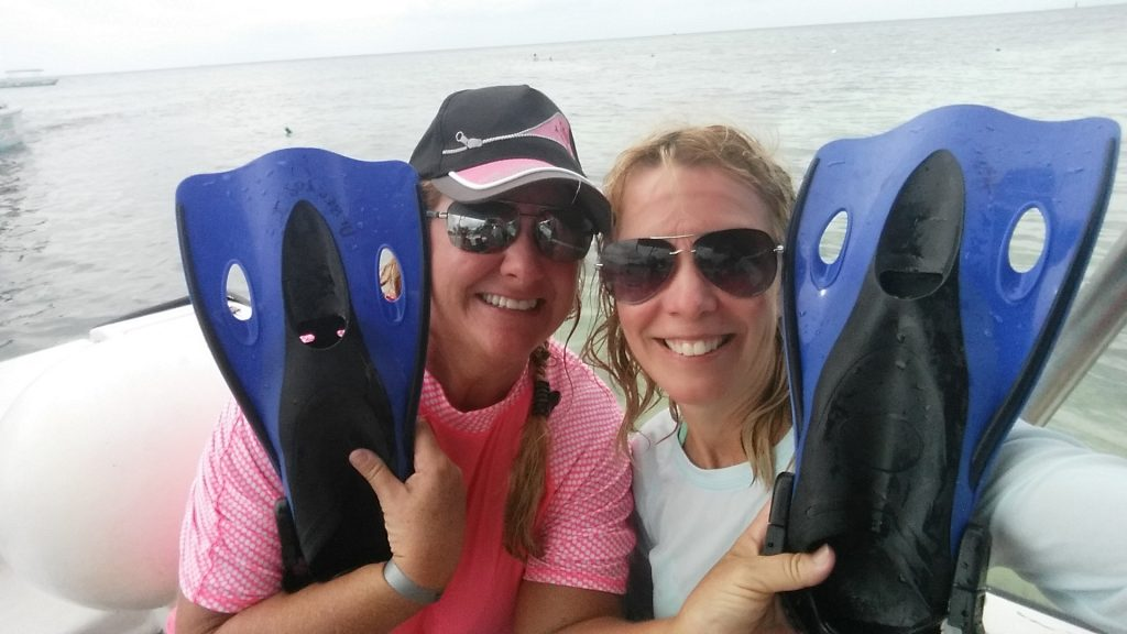 Two girls smile while holding snorkeling fins in their hands on the beach in Cozumel