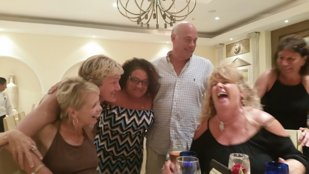 Five women and a man hug each other and laugh over dinner in a restaurant in Cozumel
