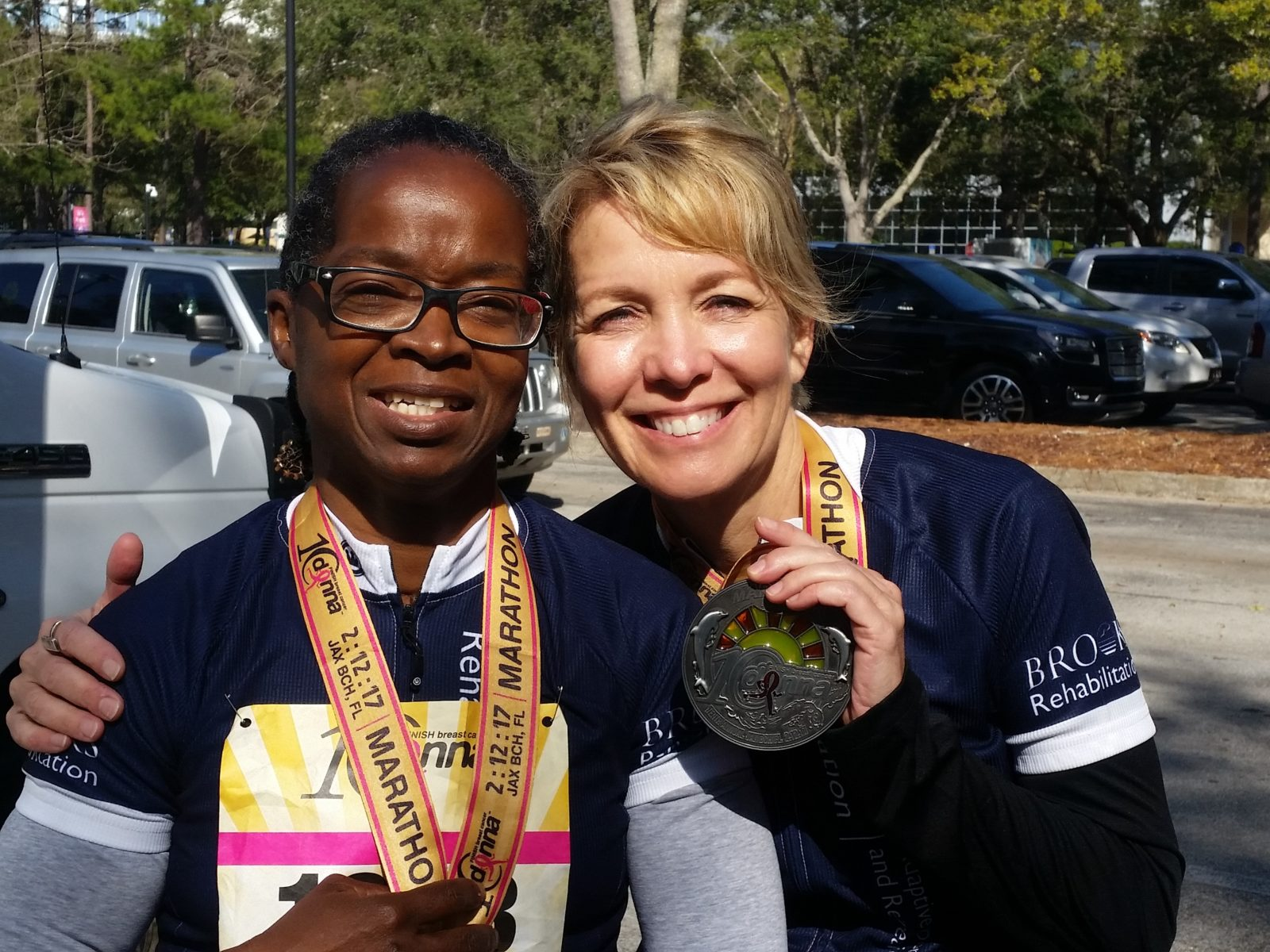 Two girls hug after biking 26.2 miles while holding their medals