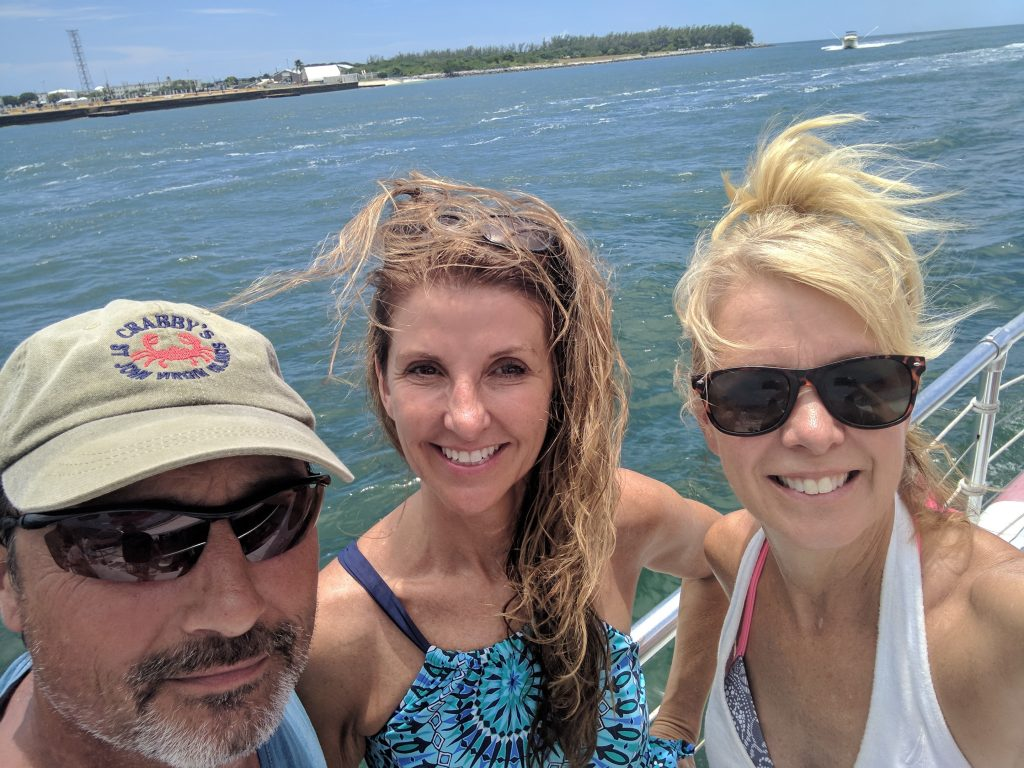 A man and two women smile for the camera on a ship as they head out on the gulf in Key West