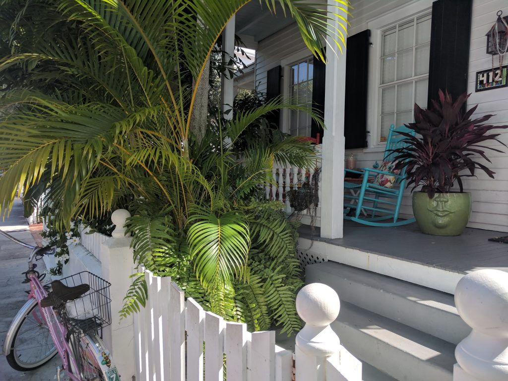 A front porch in Key West with green palms, a pink bike, a blue rocking chair and steps