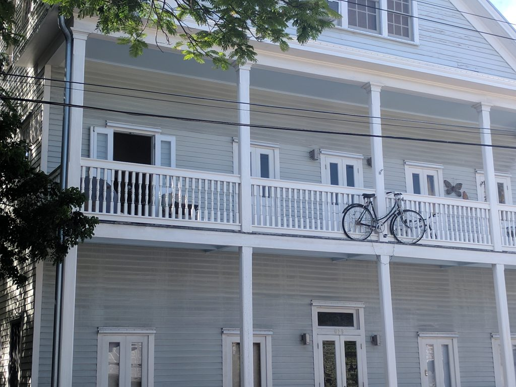 A two story house in Key West with white columns, grey siding a bike hitched to the top outside rail of the house