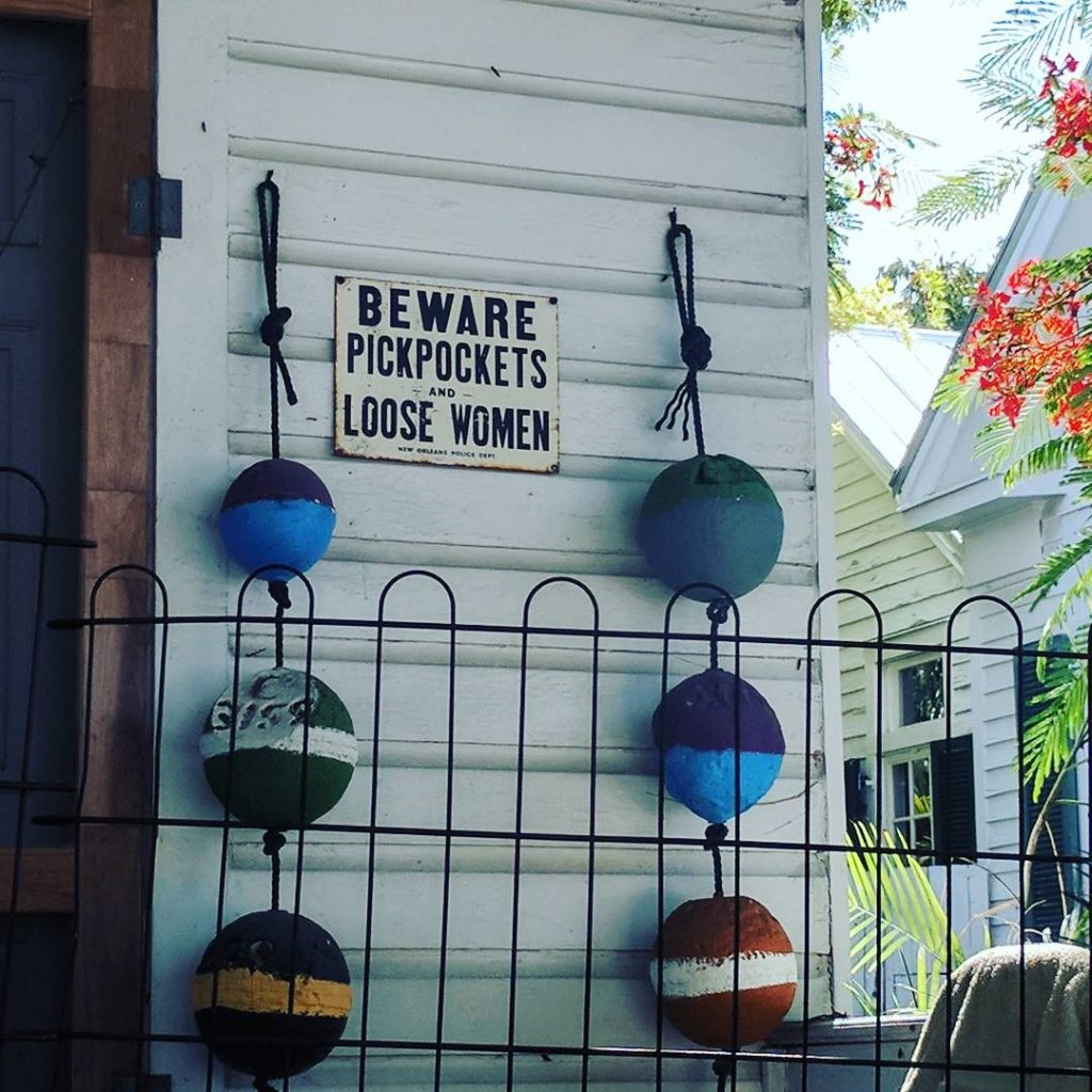 A white, front porch in Key West with a white sign and black letters sign that says Beware pickpockets and loose women