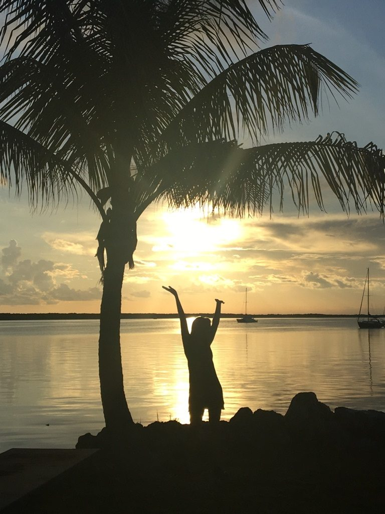 A woman throws her hands up in joy as the sun sets on the the Keys water in Key Largo and she is in silohouette