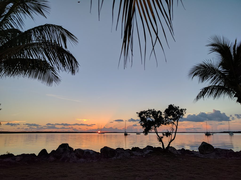 The sun sets on the water the Keys of Key Largo with blue and orange skies, palm trees in black silouette and boats on the horizon