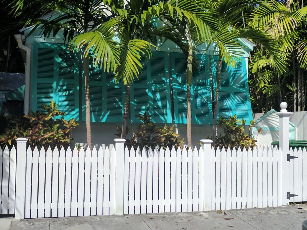 A front porch in Key West with turquoise shutters, a white picket fence and green palm trees