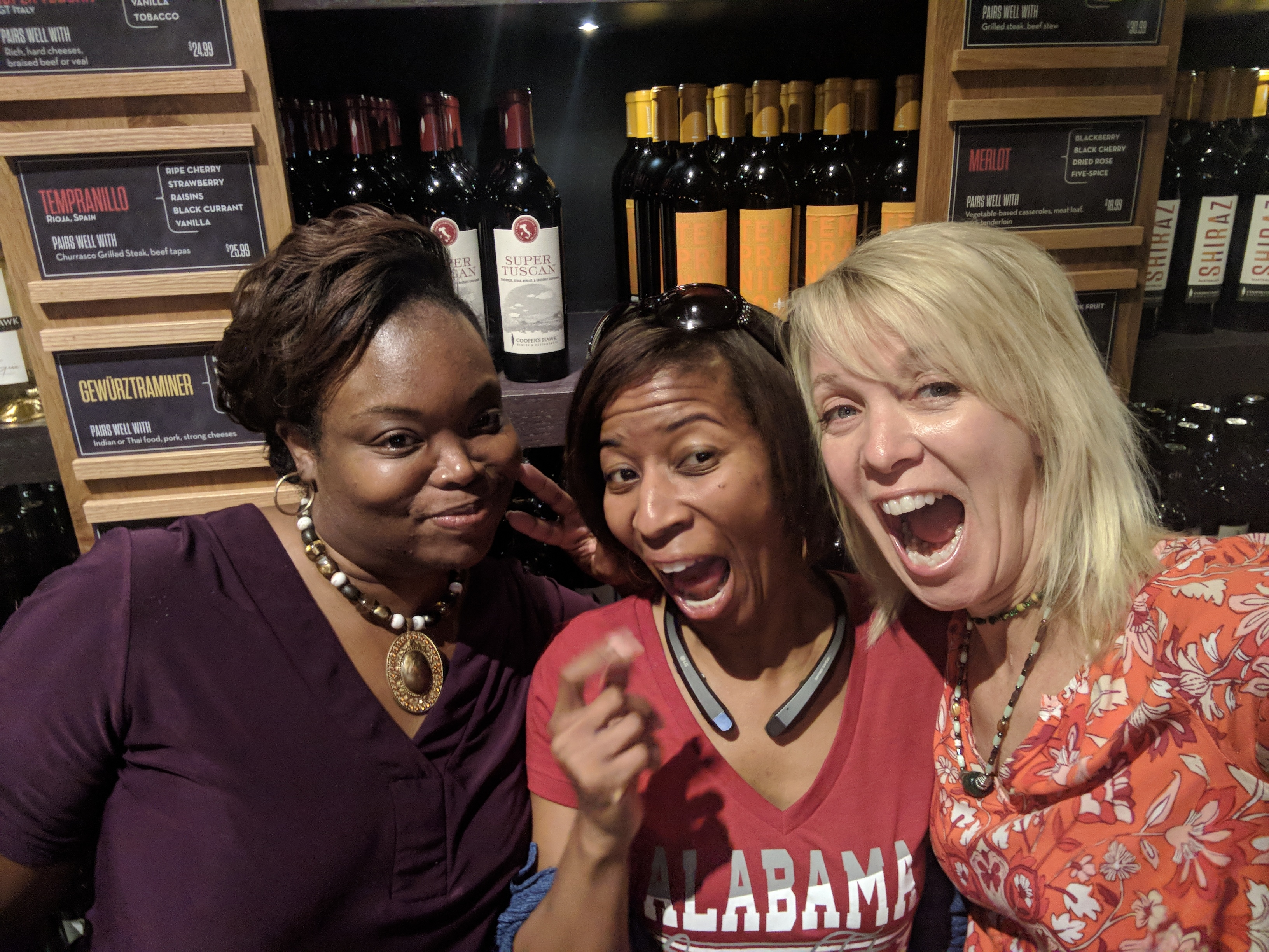 Three female friends make crazy faces in front of wine bottles at a restaurant. The Ebony Working Girl.