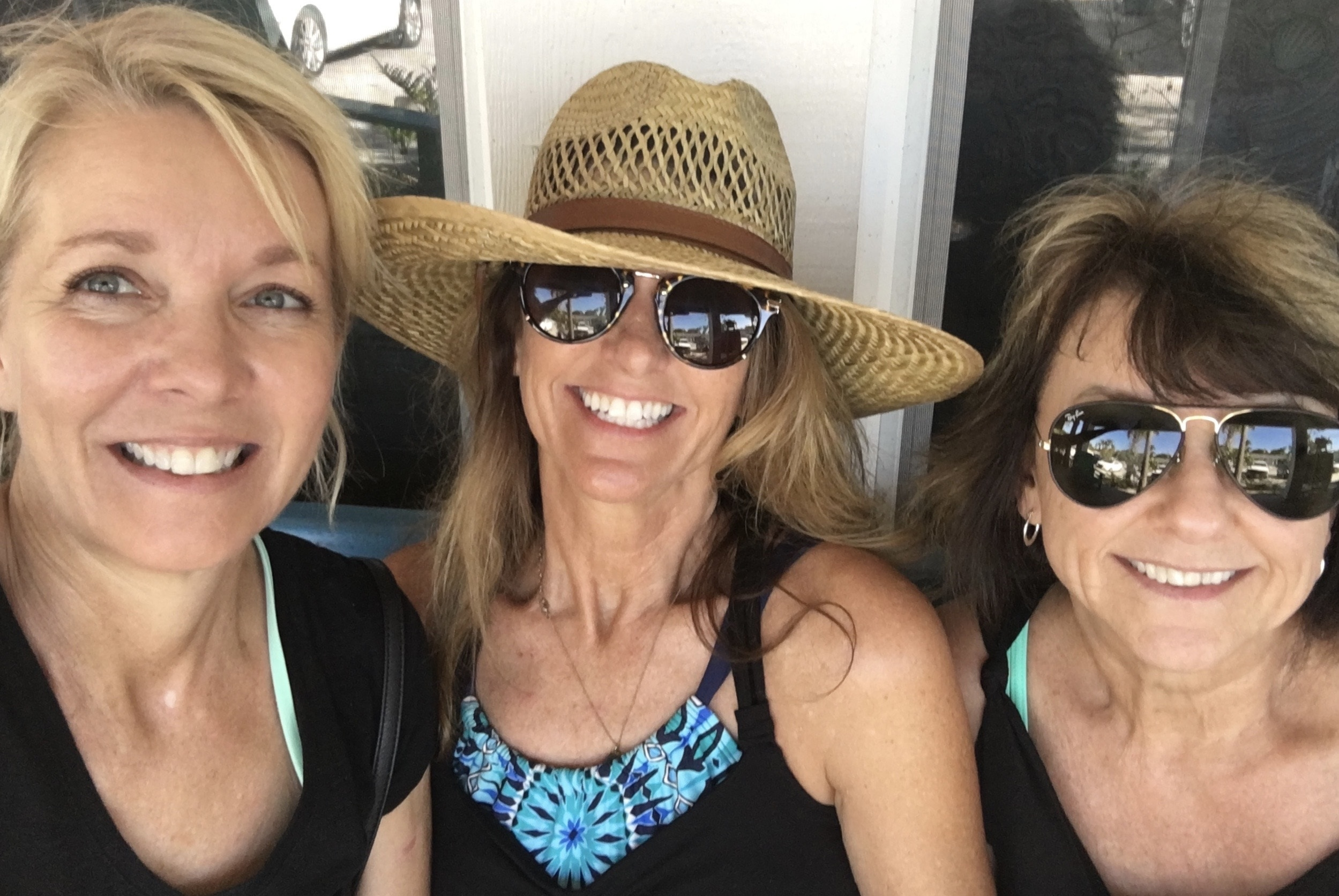 Three friends smile together in Anna Maria Island in front of unknown stores.