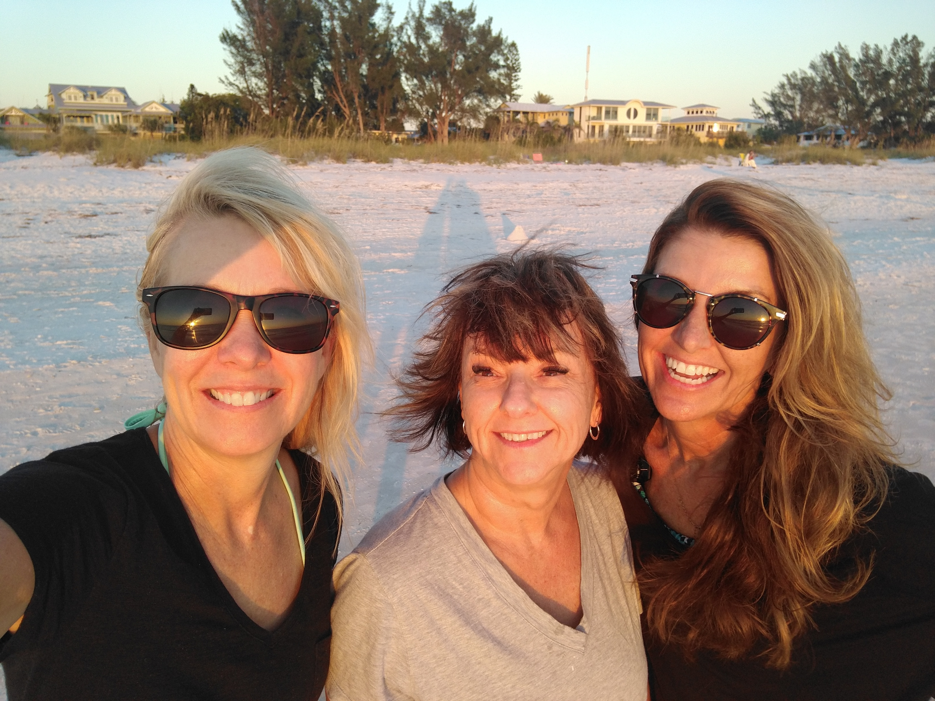 Three female friends with sunglasses smile on the beach of Anna Maria Island in Florida as the sun sets with sand in the background