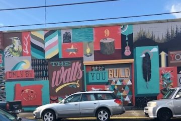 A painted wall with aqua and red graffitti and two silver cars in front