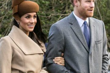 Meghan Markle is wearing a beige coat and brown hat. She is holding onto the arm of Prince Harry who is wearing a gray coat and is a member of the Royal Family.