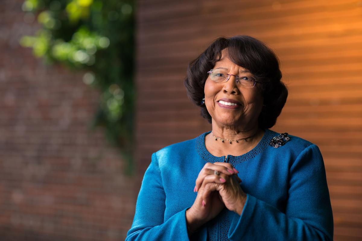 Shirley Frye, a lane changer and leader of service in Greensboro, stands in front of a wood wall in blue with her hands crossed and smiling