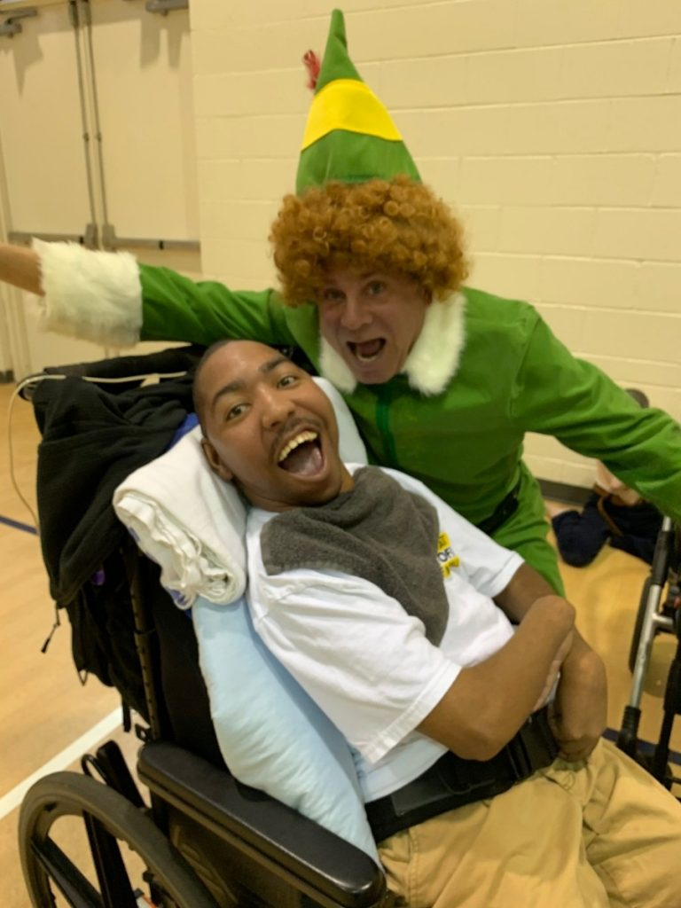 A man dressed as an elf leans over a young man in a wheelchair. Both have big smiles, giving us perspective for the holidays.