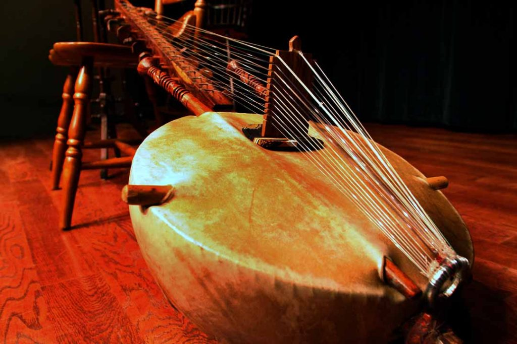 A close up photo of the kora, a musical instrument that gives us perspective on African culture. The base is round and brown and there are multiple strings that go up to a long wooden neck.