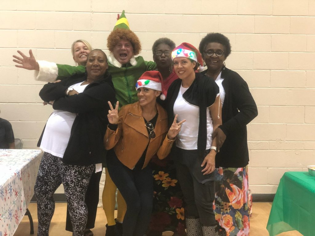 Six women pose with a man dressed as an elf. They are all smiling and standing against a beige brick wall.