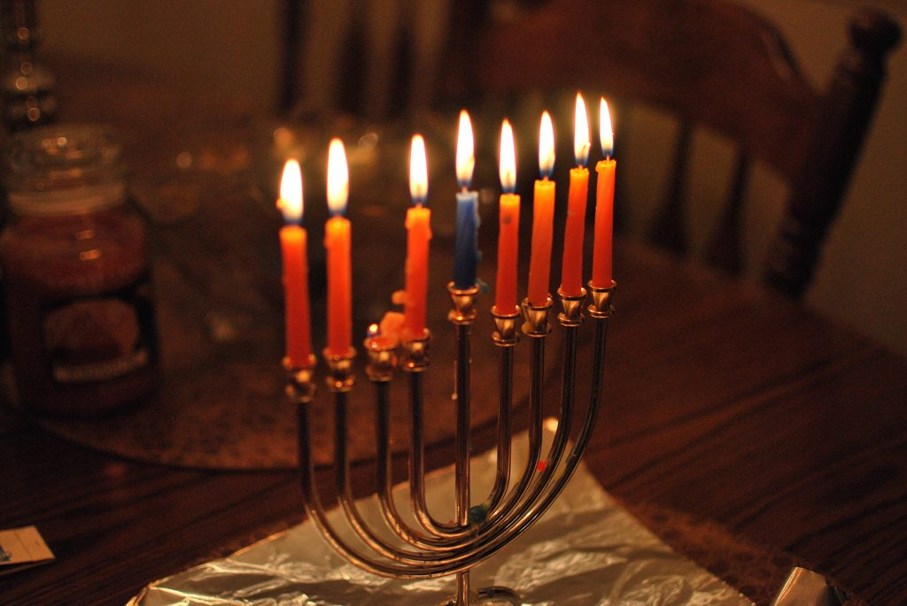 A gold colored menorah holds eight burning candles to celebrate Hanukkah. There are seven orange and one blue and the menorah sits on a wood table. Hanukah gives us perspective on the Jewish community.