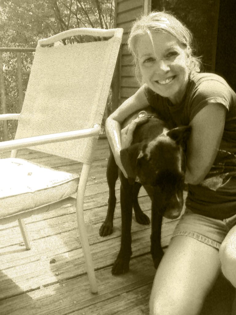 A white women hugs a two-year-old black lab. They are on a deck next to a chair.