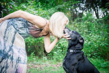 A white woman in a multi-colored sundress kisses her black lab son on the lips as he sits.