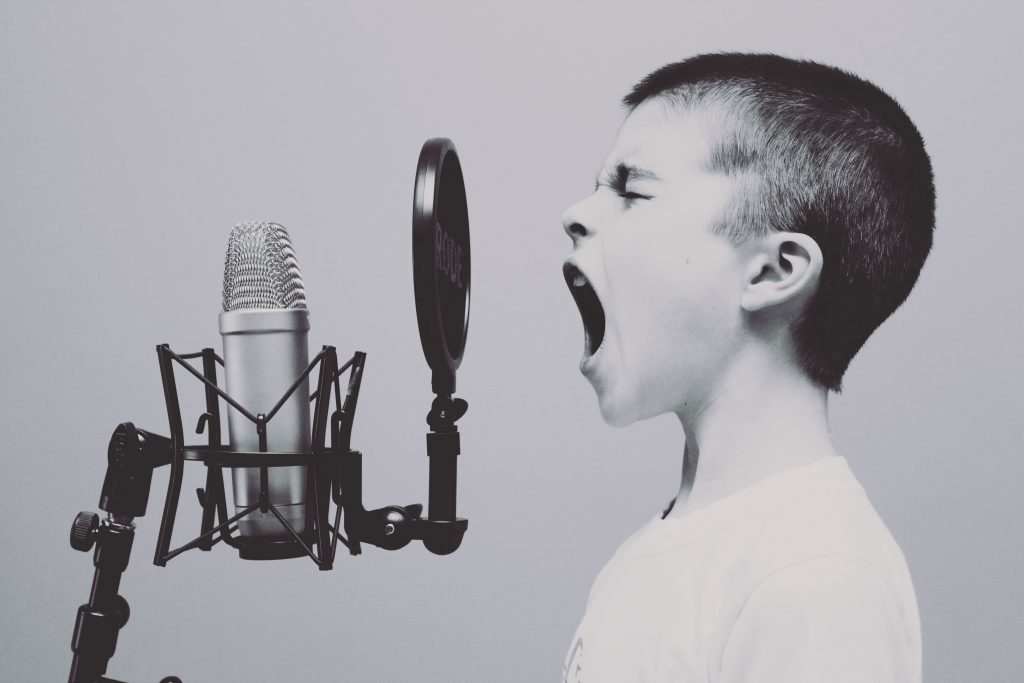 A young boy shouts into an old fashioned microphone with his eyes closed to reflect Voice in branding.