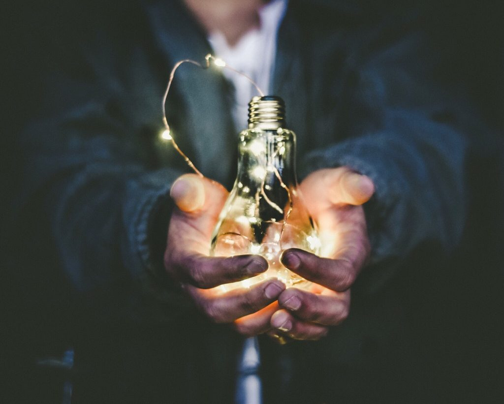 A man holds a light bulb in his hand to reflect the Value in branding.