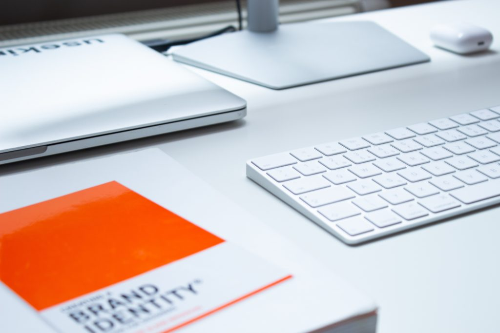 In order to have a plan to scale your business, owners should think about online reach. The photo includes the top of a white desk with a book, wireless keyboard, laptop and the stand of a screen monitor.