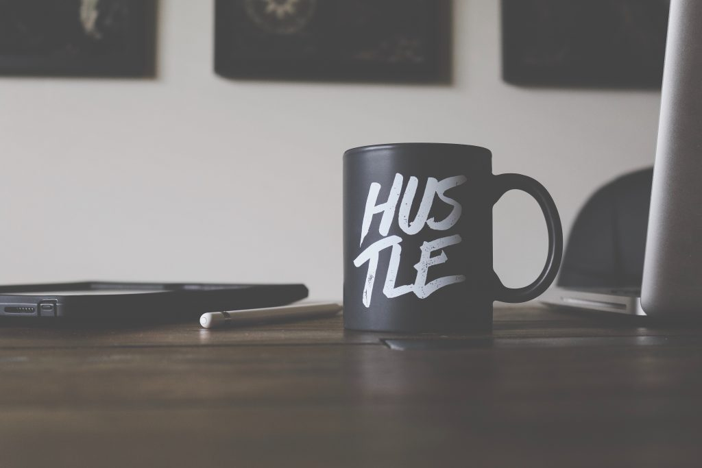 In order to create a plan to scale  your business, you need to have an entrepreneurial mindset. This photo of a black coffee mug with the word hustle in white demonstrates this.