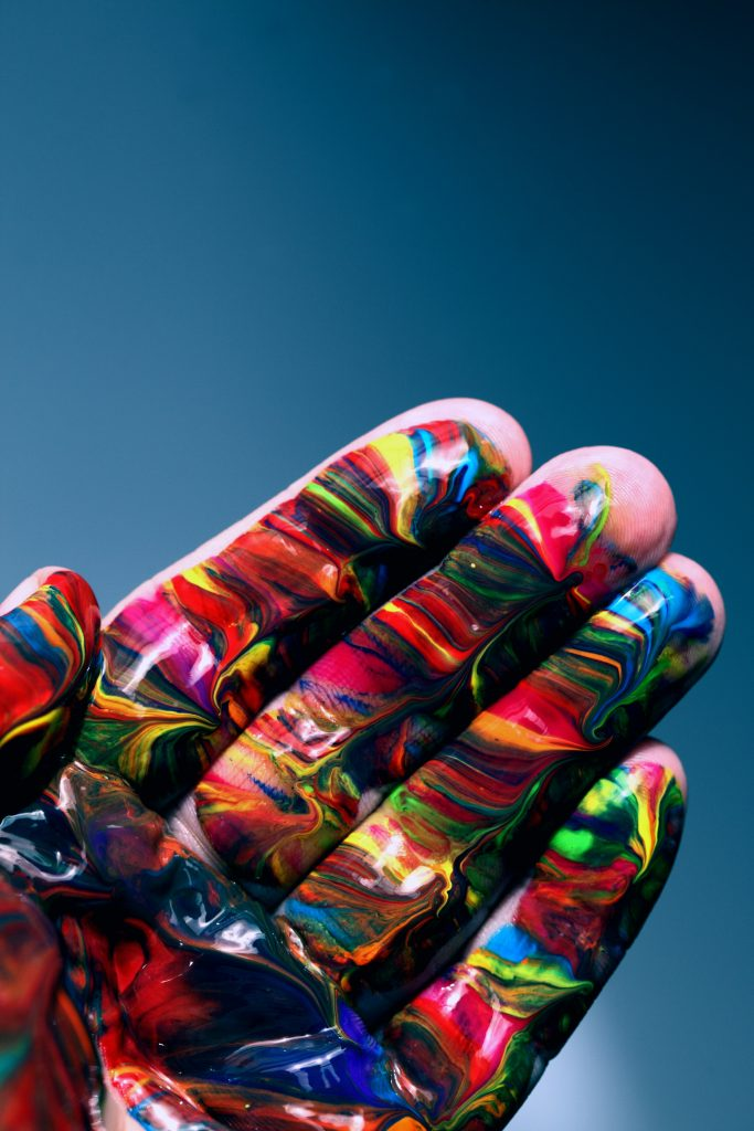 A white hand is painted with a rainbow kaleidoscope across the palm to reflect DEB which is diversity, equity and belonging