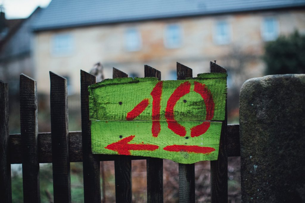 to demonstrate a great company experience during the coronavirus, a green hand made sign with the red numbering of 10 hangs form a black picket fence