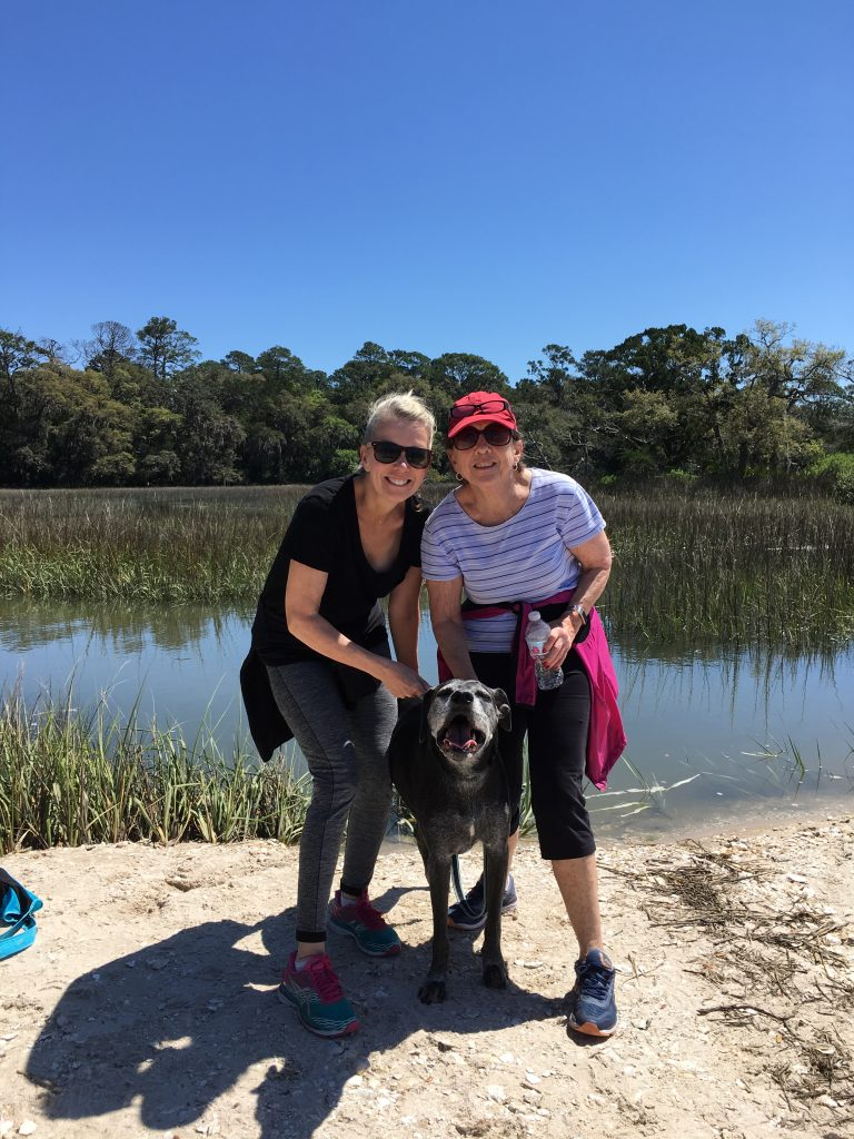two women stand with a black lab at the water's edge at Guana Reserve with white sand, blue skies and green trees
