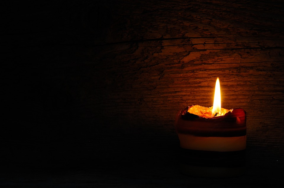 A white flame burns against a black background from a burning candle
