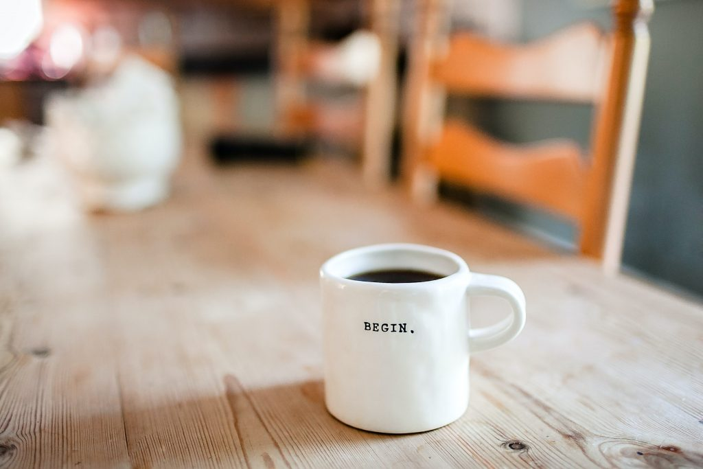 A white coffee cup mug with the words Begin sits on a wood table