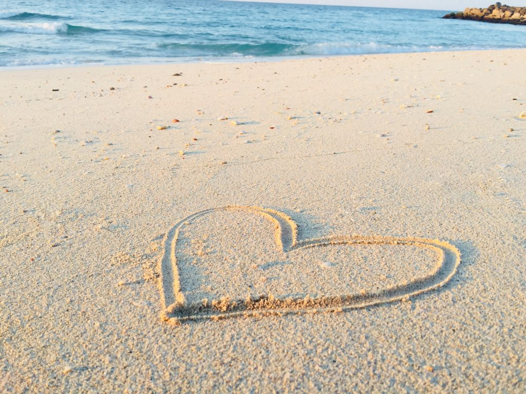 a heart shape is drawn into the sane with a small view of blue water in the background
