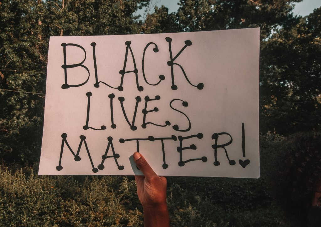 A black hand holds up a white sign with black letters that says Black Lives Matter