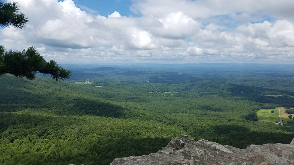 A view from the top of Hanging Rock in North Carolina with blue skies, white clouds and the tops of green trees