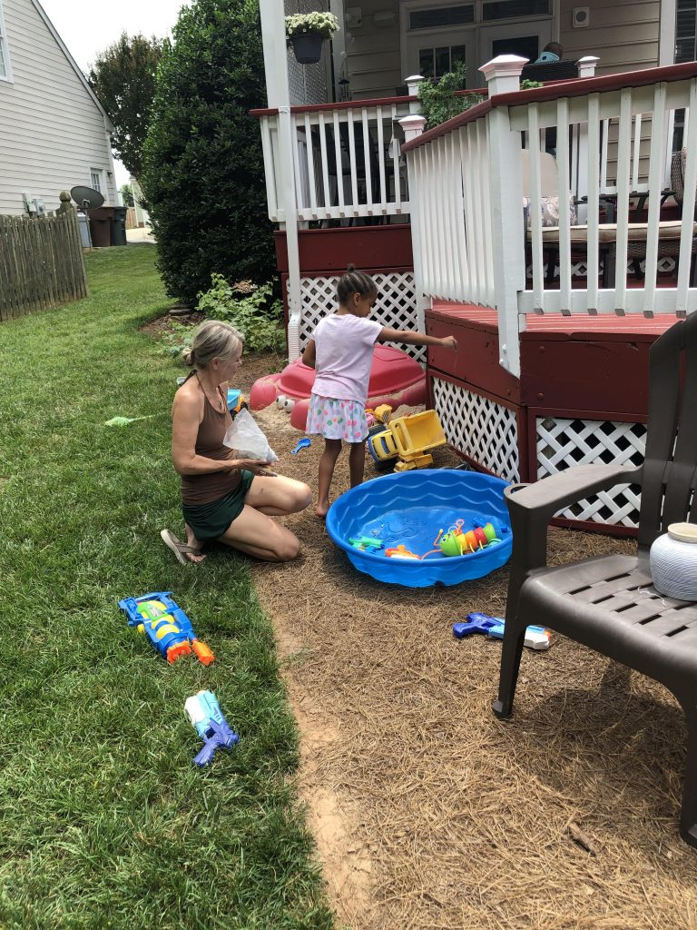 A woman kneels on a green lawn while a child sprinkles dog ashes by her plastic pool.