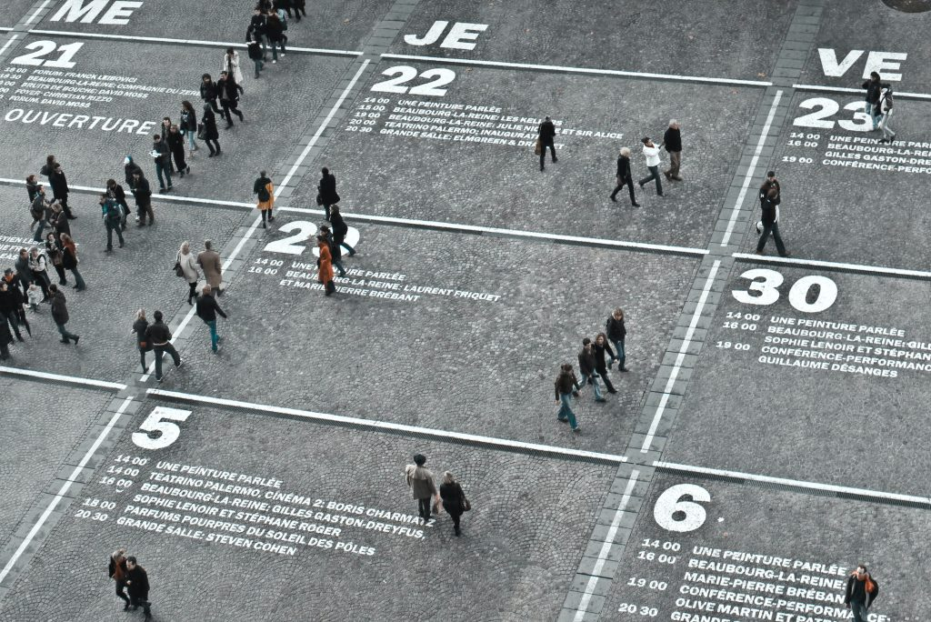 a high shot view shows unidentified persons in black standing in blocks drawn on the pavement with numbers as a way to demonstrate the web as part of branding 101 basics