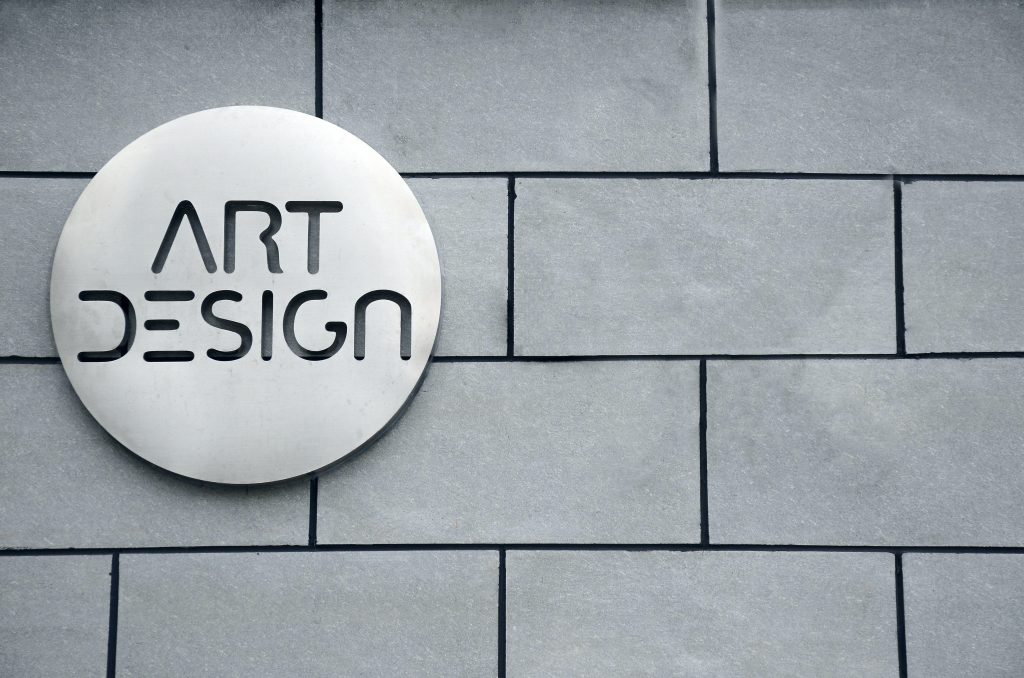 a gray brick wall with a button on top that says art design to represent logo in branding 101 basics