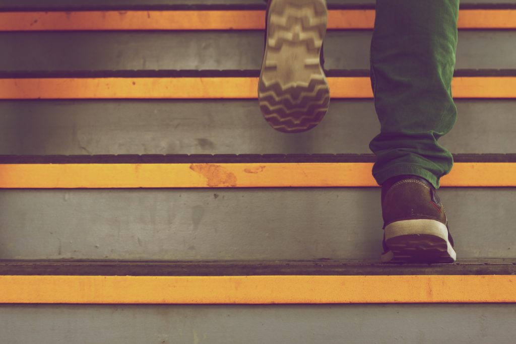 a male steps up stairs as we see only his feet with boots on cement steps