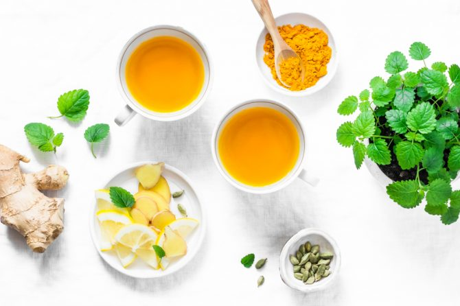 on overhead photo of a table with herbs, lemon, nuts and tea to demonstrate an anti-inflammatory diet