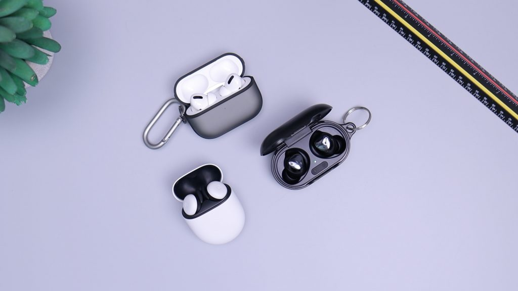 three charging cases with ear buds sit on a white table
