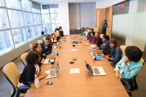 A large group of people with various genders and ethnicity sit around a confernce table with papers and laptops in front of them
